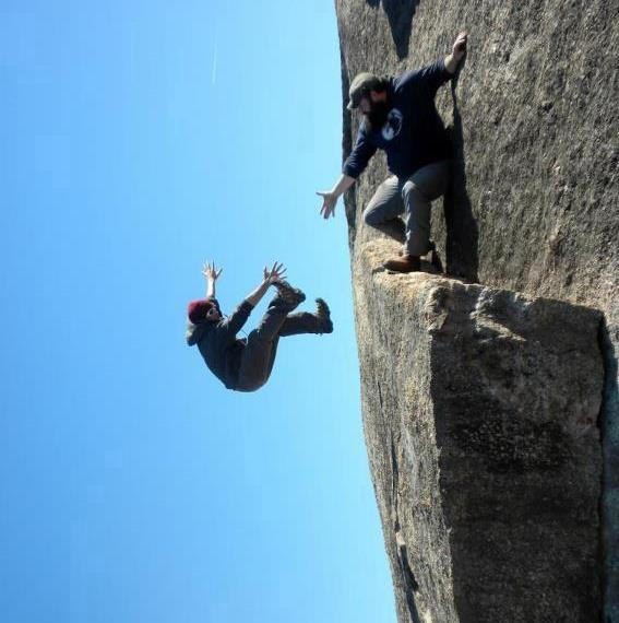 Image: A picture of two men that makes it look like one man is falling off a cliff but in reality, it's just taken at a funny angle