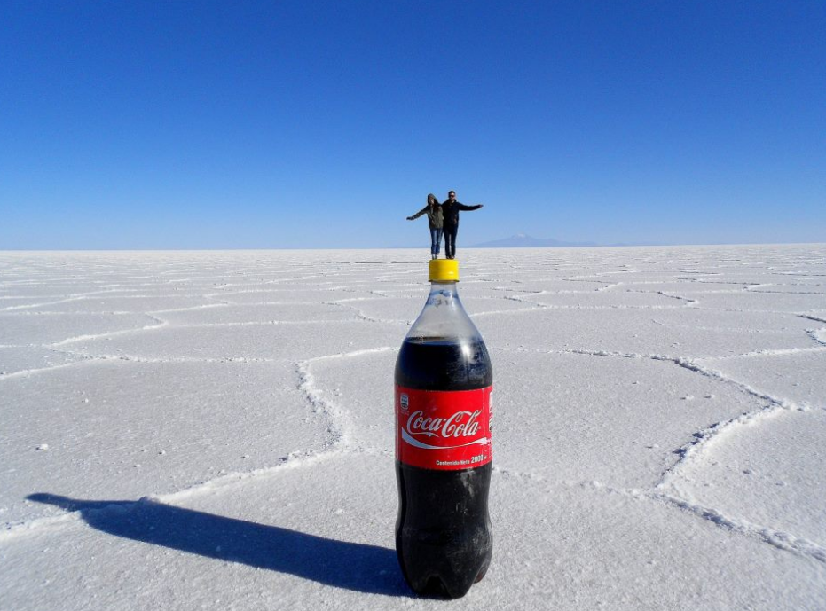 Image: This pic's perspective makes it look like a couple is standing on top of a Coca Cola lid