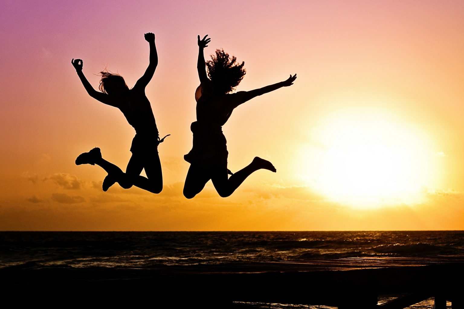 Image: happy jumping people at sunset