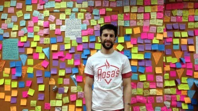 Image: Mason Wartman stands in front of wall of sticky notes