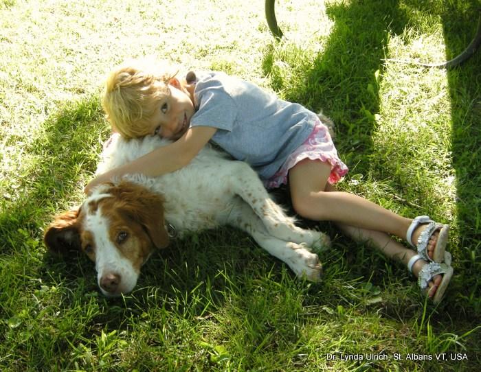Image: A little girl loving a good dog