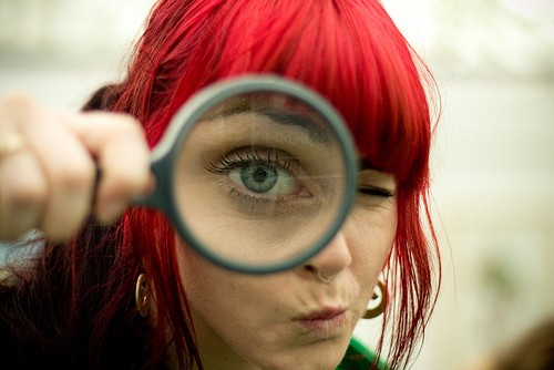Image: red haired woman with magnifying glass
