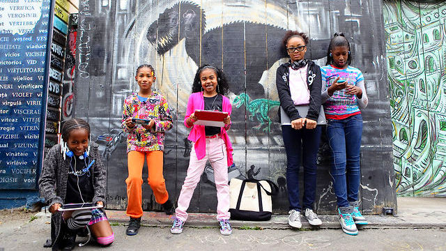Image: A group of 5 young girls all holding laptops and tablets in front of a vividly painted wall