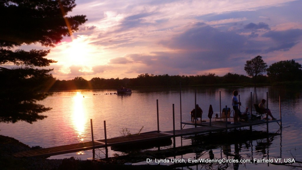 Image: dock at sunset. Beautiful purple and pink sky, sun shining on the lake, now a light pink shade because of the sunset