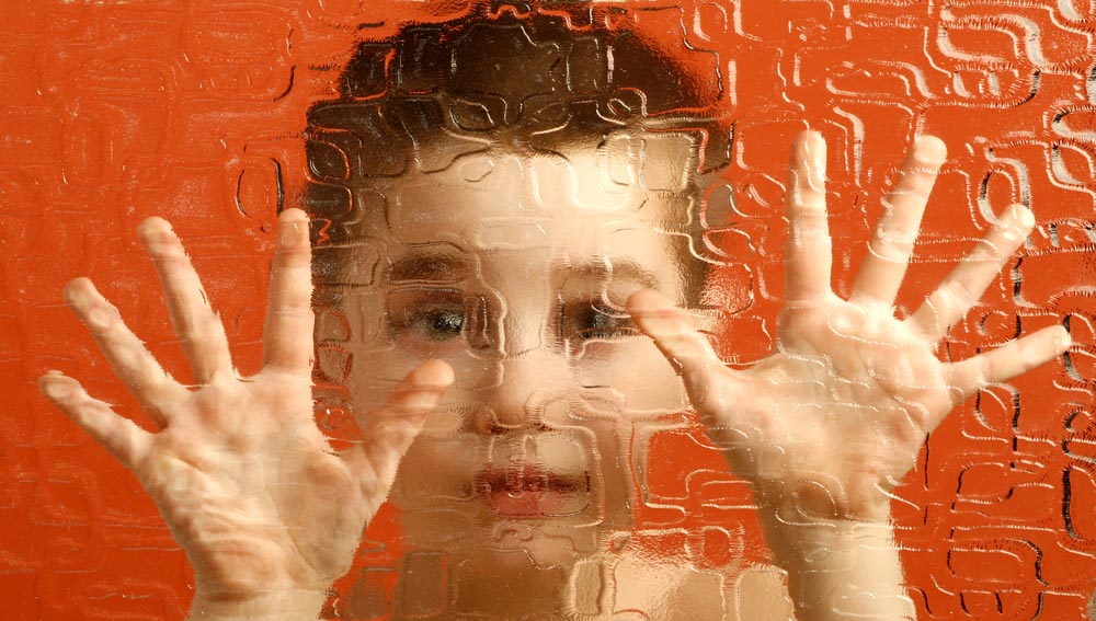 Image: Boy looking through patterned glass
