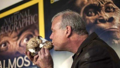 Image: Man kisses early human skull