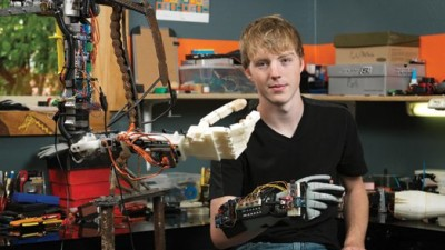 Image: Teen posing with robotic arm