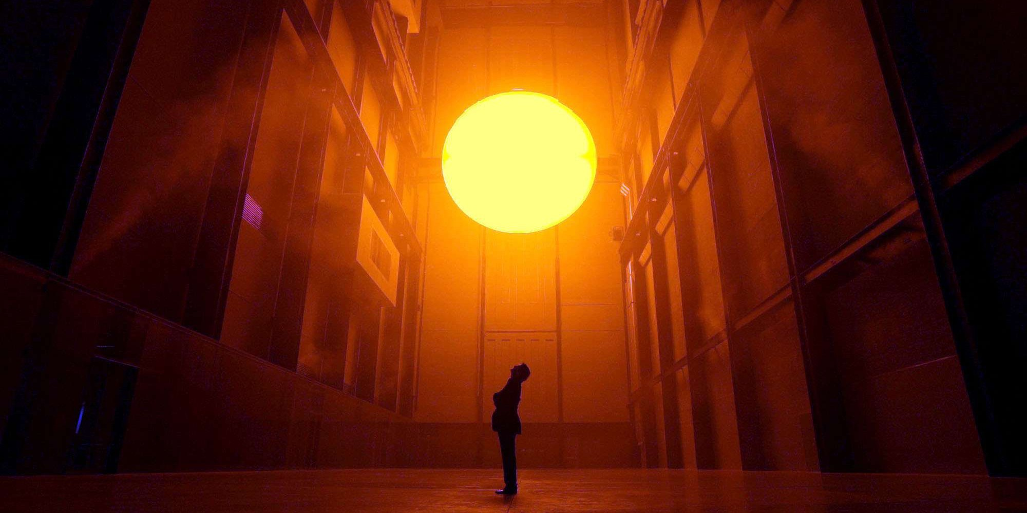 """Danish environmental sculptor Olafur Eliasson, stands in the Turbine Hall at the Tate Modern art museum in London and looks up at his art work entitled """"The Weather Project,"""" in this Oct. 15, 2003 file photo. Eliasson has used mirrors, light, sound and mist to create a monochrome space that exposes and confronts the visitor."""