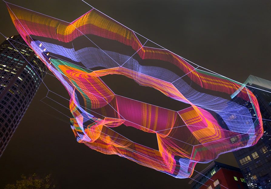 """""""As If It Were Already Here"""" net sculpture by Janet Echelman lit with many colors at night."""