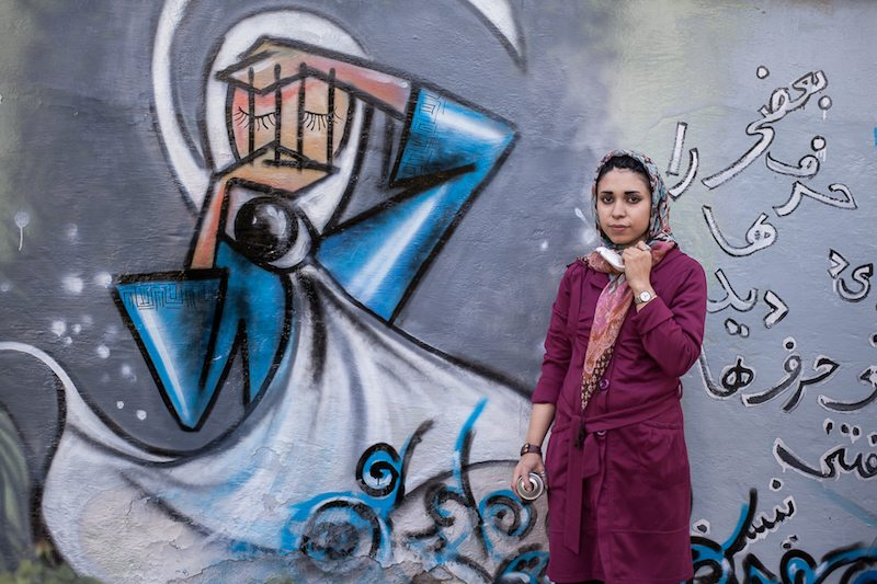 Image: Afghan artist Shamisa Hassani standing in front of her graffiti art depicting a woman with bars over her face
