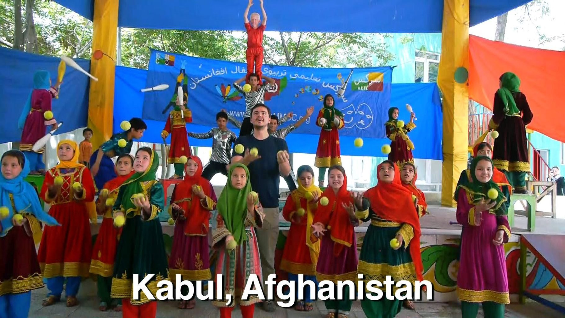 """Image: Matt Harding, head of """"Where the Heck is Matt?"""", is dancing with young girls in Kabul Afghanisatan"""