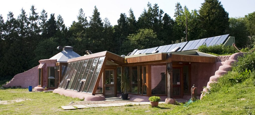 Image: the Brighton Earthship, a home tucked into a hillside with large windows in the front