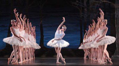 Image: Huston Ballet production of Swan Lake, principal dancer centered with corps de ballet surrounding