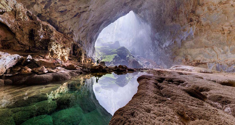Image: Hang Son Doong Cave entrance to Underground Rainforest with a person standing above a water pool