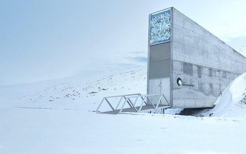 Image: The entrance to the Svalbard Seed Vault, a massive concrete structure jutting out of the side of a snowy mountain
