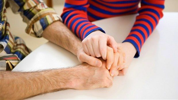 Image: Two people holding hands, one comforting the other