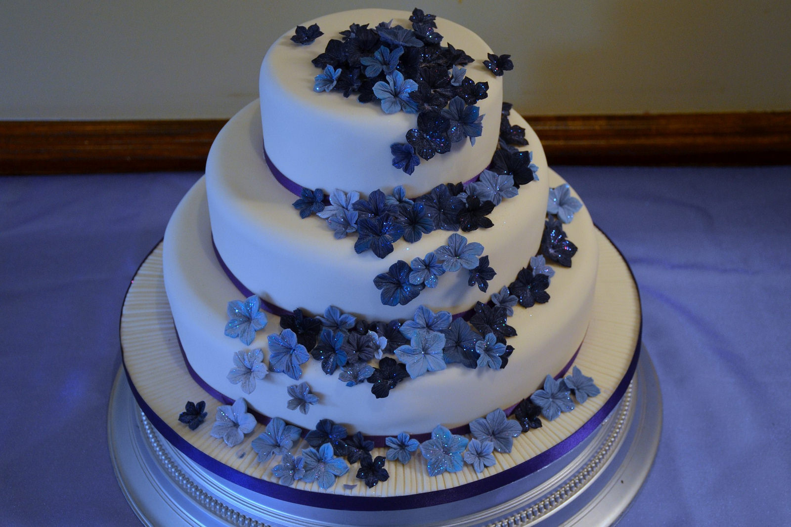 Image: A beautiful 3 tier cake with blue sugar flowers