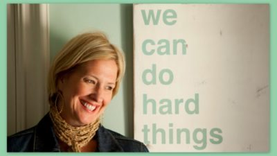 "Image: Brene Brown sitting before a sign that says, ""We can do hard things."""