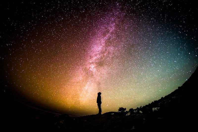 Image: A silhouette of a person looking up at the stars beyond the milky way, one of the discoveries of the past century