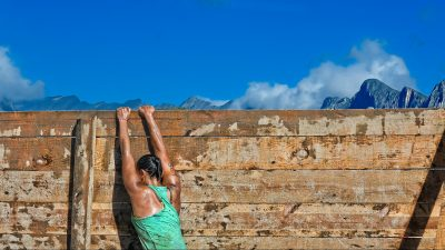 Image: Woman climbing up a tall wall with mountains and clouds in the background