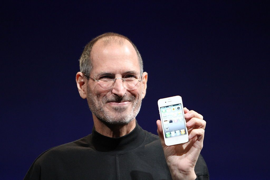 Image: Steve Jobs holding an early model iPhone.