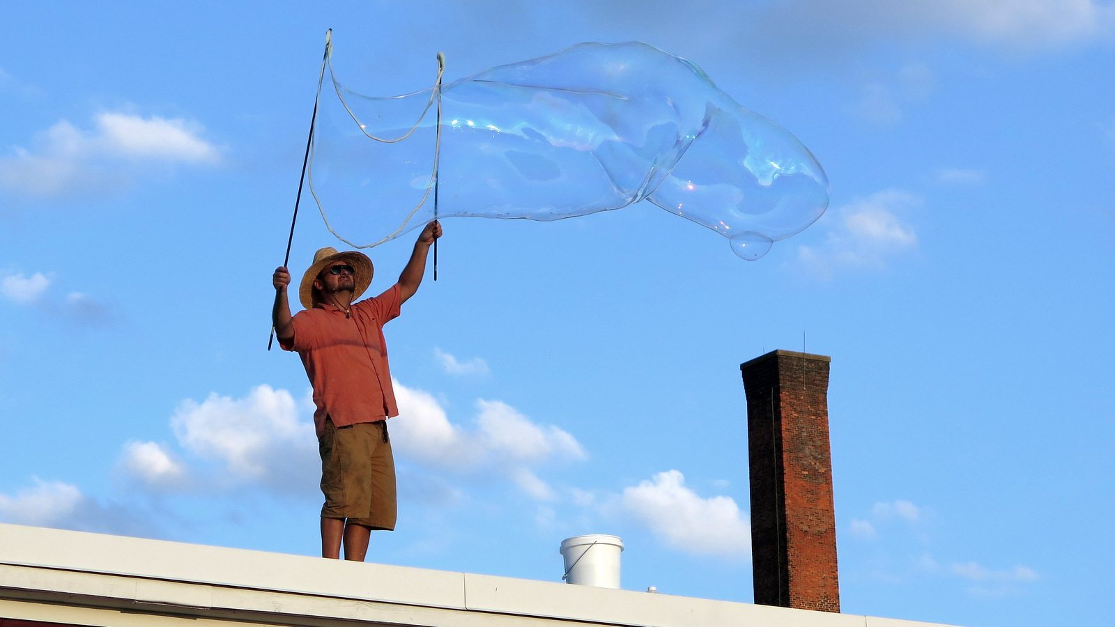 Image: Man on a roof creating a giant soap bubble