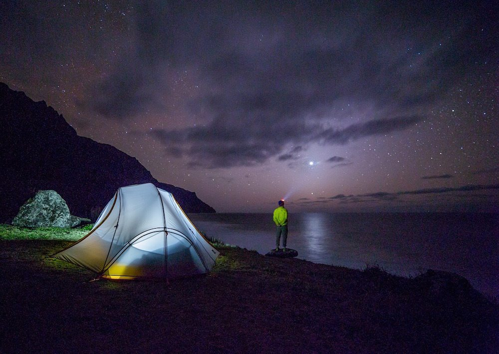 Image: Tent beside a lake lit up at night with a hiker looking up at the sky