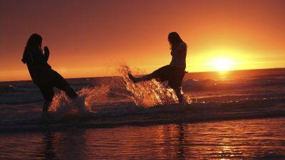 Image: Two girls at sunset on a beach splashing water