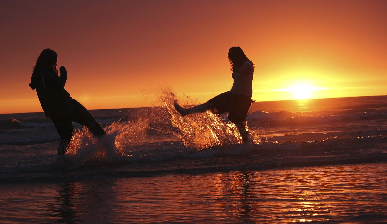 Image: Two girls at sunset on a beach splashing water