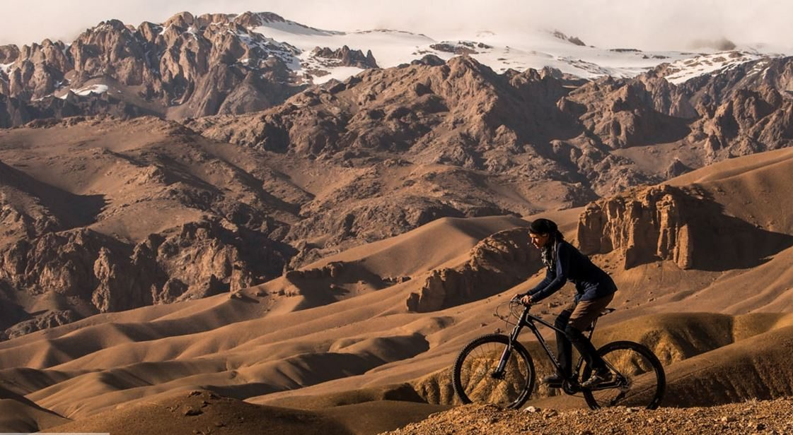 Image: Shannon Galpin on a bicycle win a beautiful Afghan mountain setting