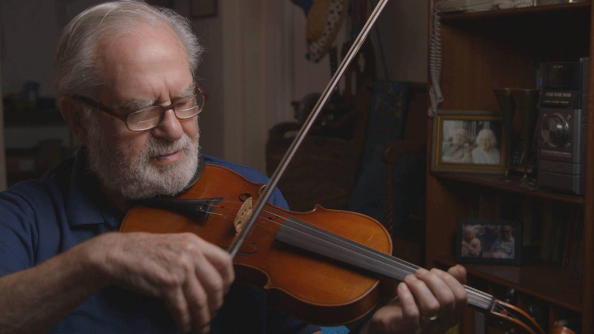 "Image: Joseph Feingold playing his violin in the film ""Joe's Violin"""