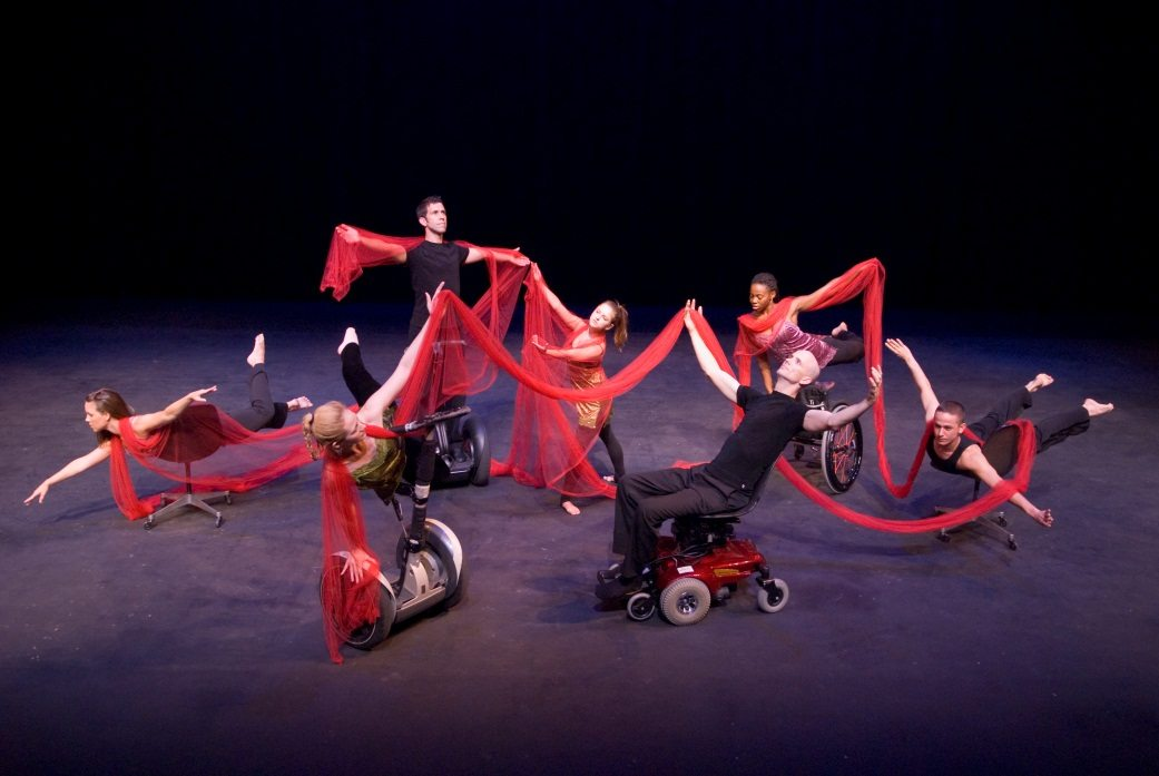 Image: mixed ability dancers dancing together onstage some in early versions of the Rolling Dance Chair