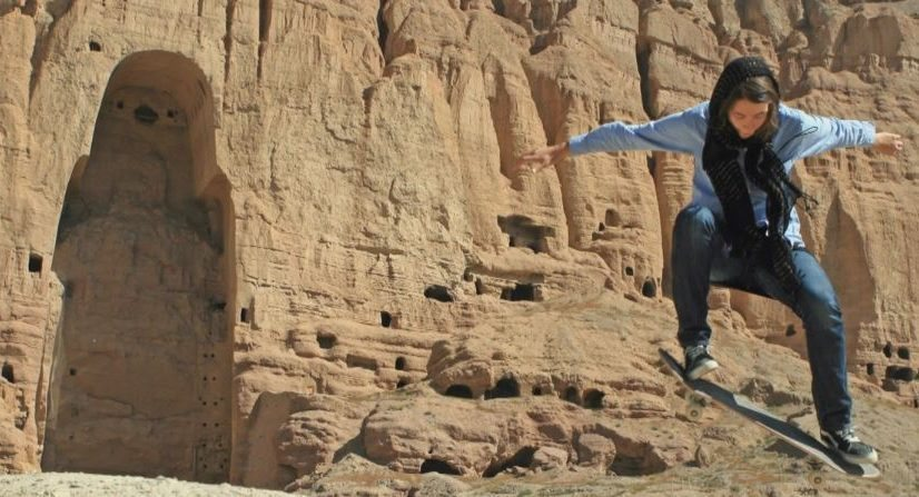 Image: Young skateboarding girl jumping in front of an ancient monument