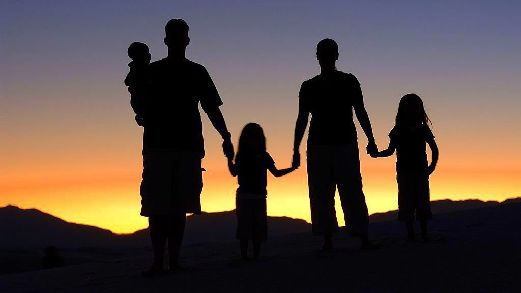 Image: A silhouette of a family against the sunset