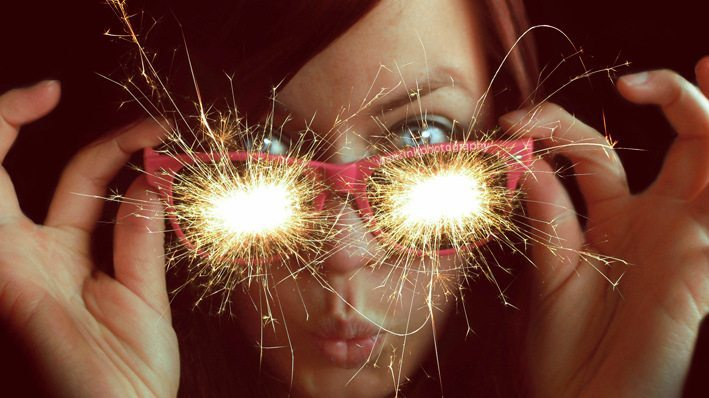Image: Woman holding glasses to her face with sparklers coming out to the lenses