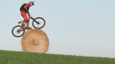 Image: Stunt Cyclist Danny MacAskill riding atop a round bail of hay, rolling down a hill