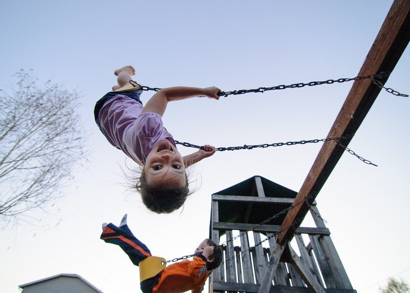 Image: Kids swinging and one upside down