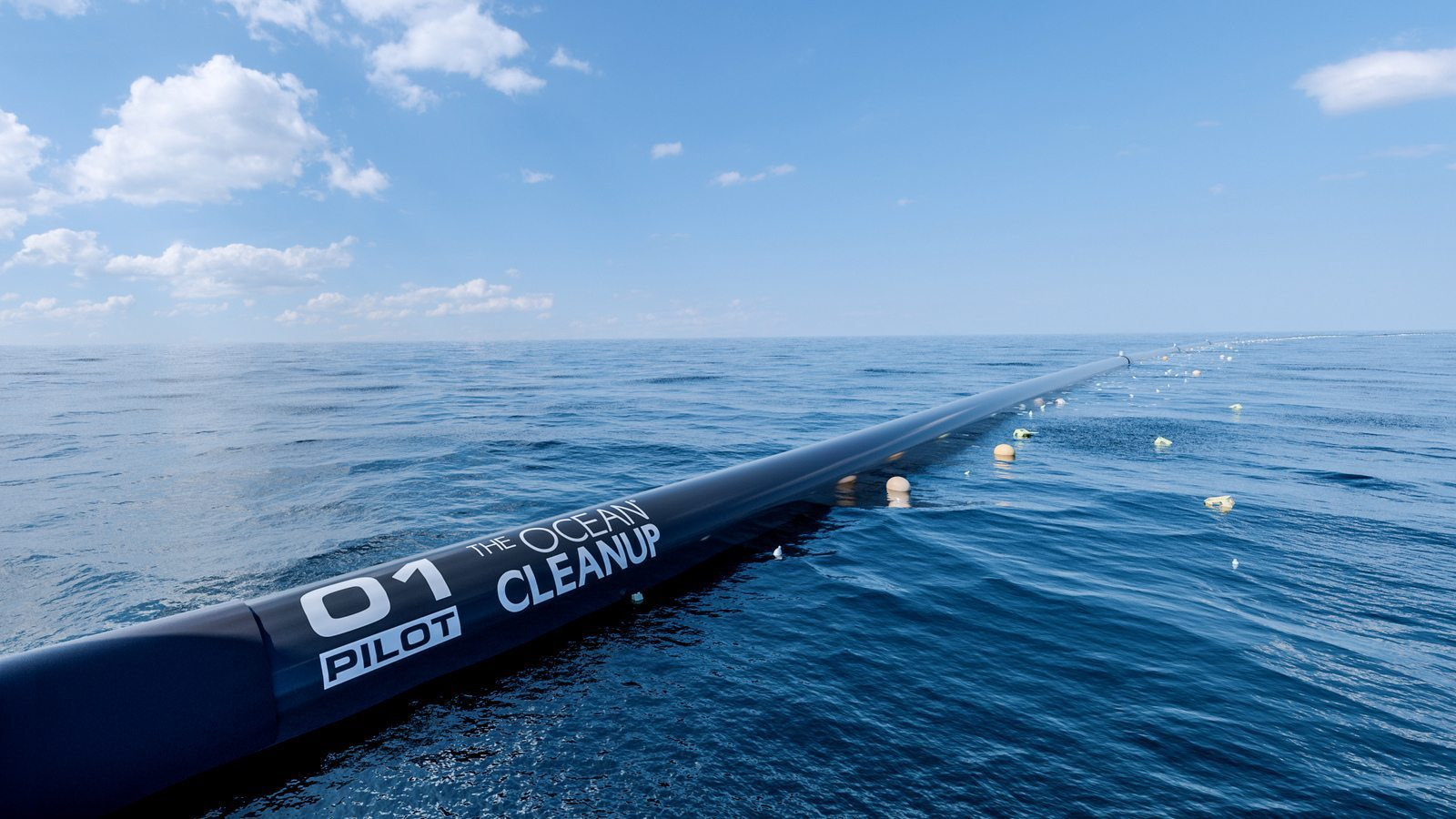 Image: Ocean Cleanup Project boom array in the ocean with collected plastic floating in it