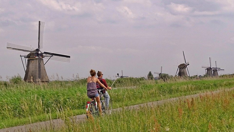 Image: couple biking through windmills