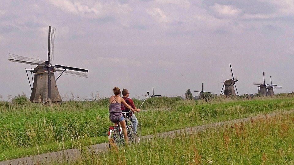 Image: couple biking through windmills