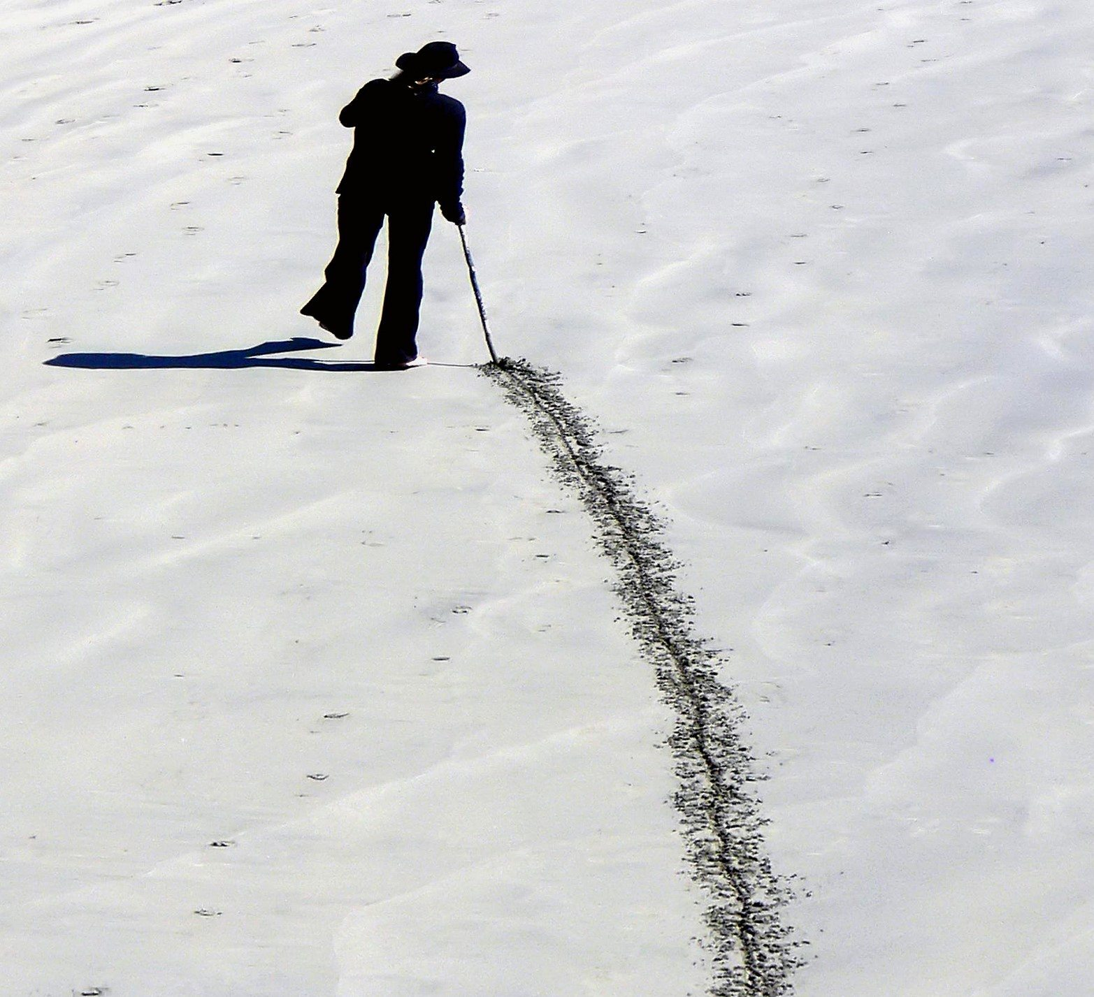 Image: man putting a line in the sand with a stick