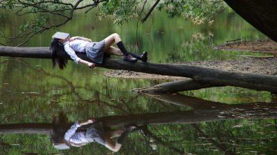 Image: Woman asleep on a tree limb over a pond