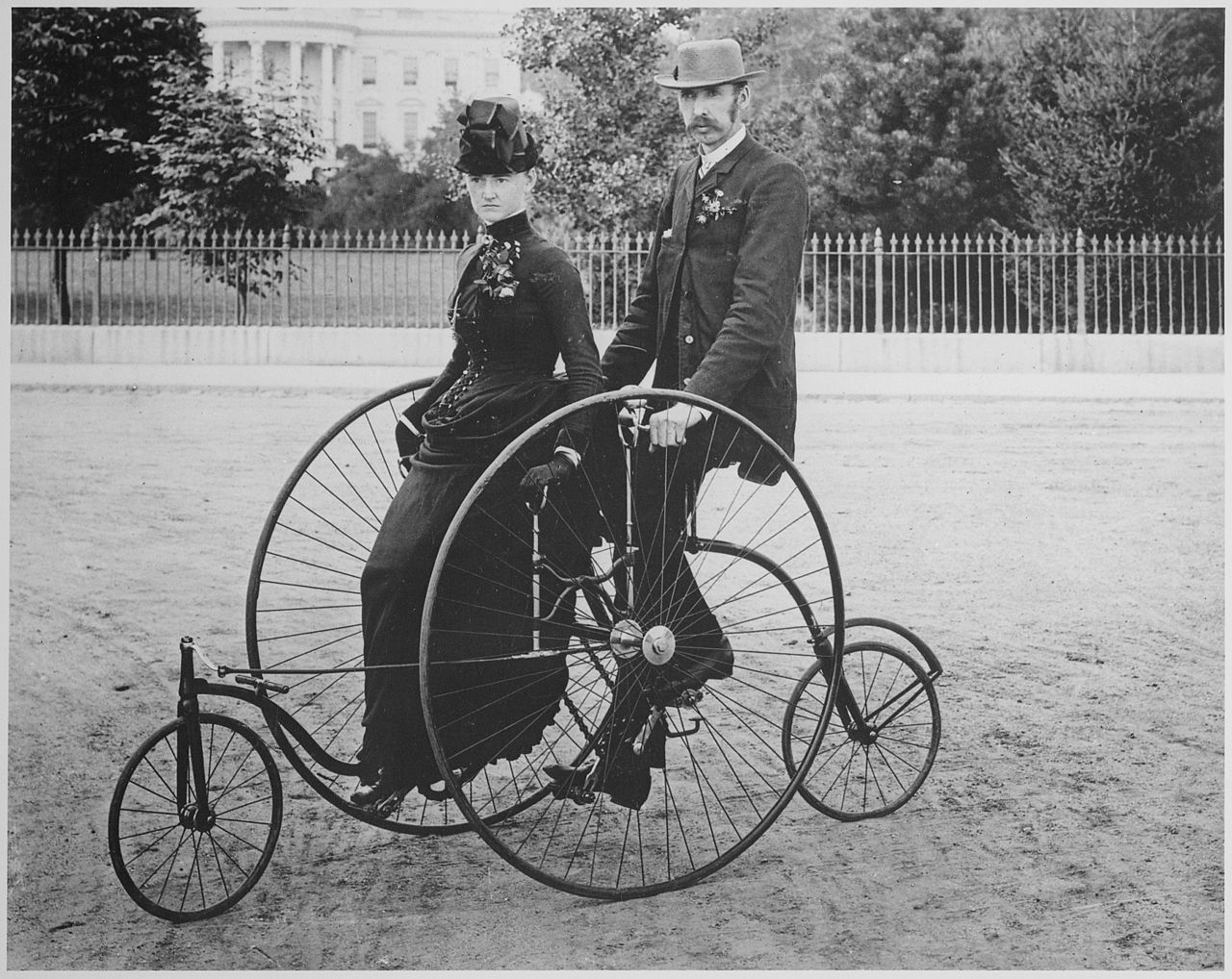 Image: A HUGE wheeled bicycle fro 1886 with smartly dressed people riding it together.