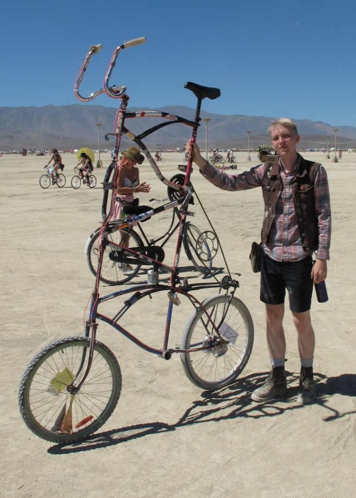 Image: A cyclist stands by his bike on the beach and the bike is two feet taller than he is!