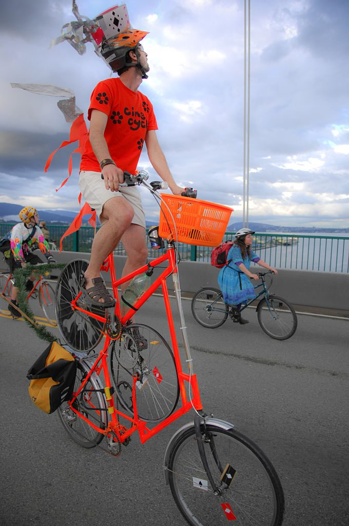 Image: Man in a bright orange top hat, on a bright orange, one of many, tall bikes sitting 10 feet in the air.