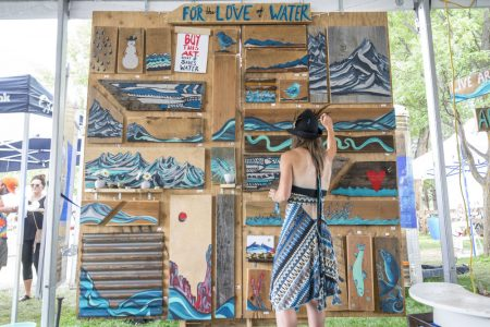 Image: Artist and their mural consisting of small paintings to sell off to raise money for Water Conservation