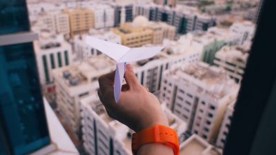 Image: Hand throwing a paper airplane out of a window over a city