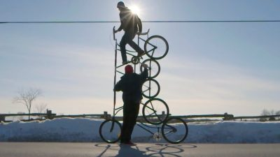 """Image: A person riding one of many """"Tall Bikes"""" that is 5 wheels tall."""