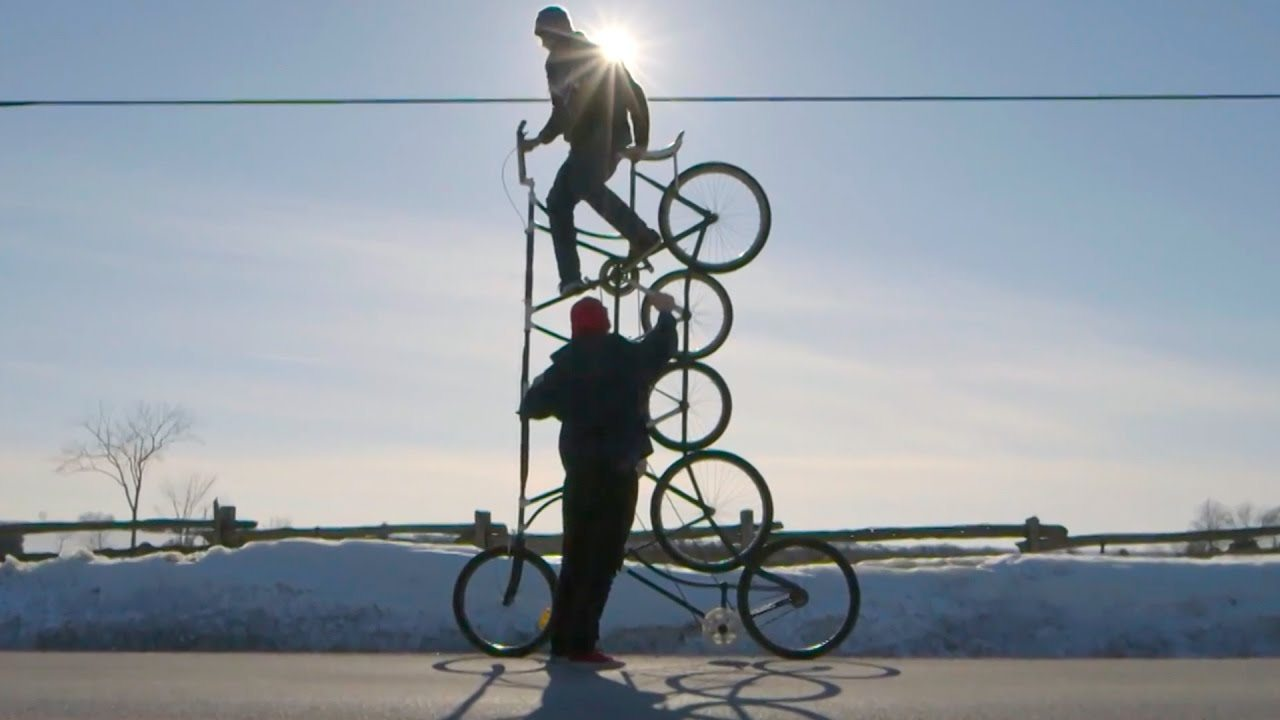 "Image: A person riding a ""Tall Bike"" that is 5 wheels tall."