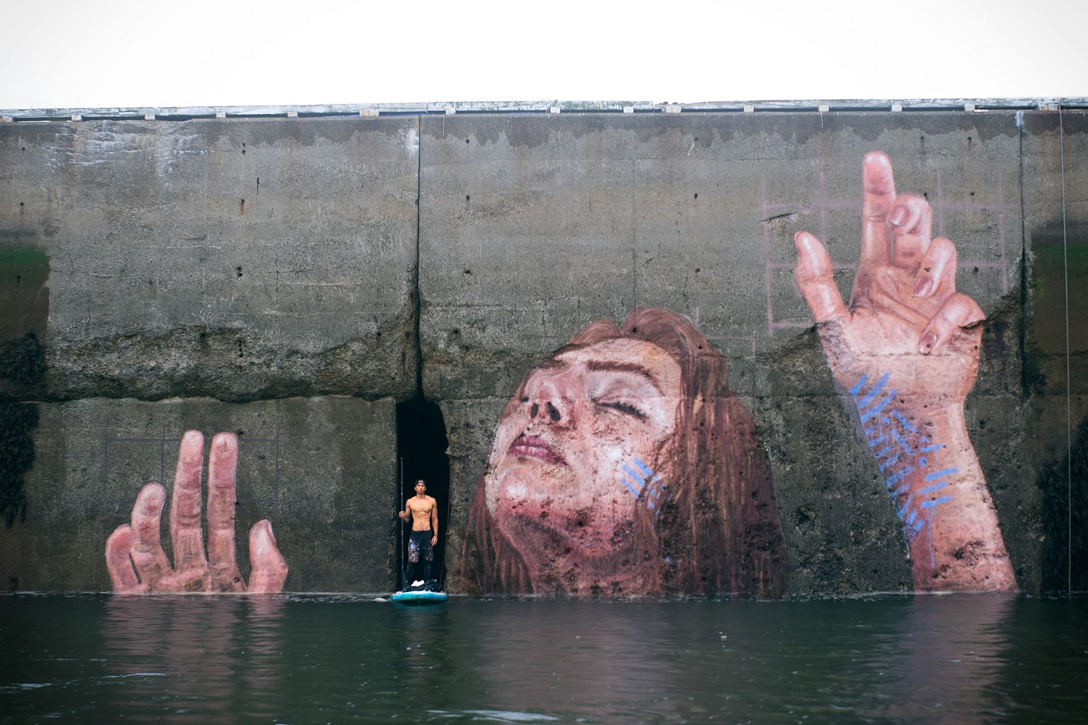 Image: Artist standing on their paddleboard in the forefront of their creation: a massive, stunning painting of a woman reaching out of the waters.